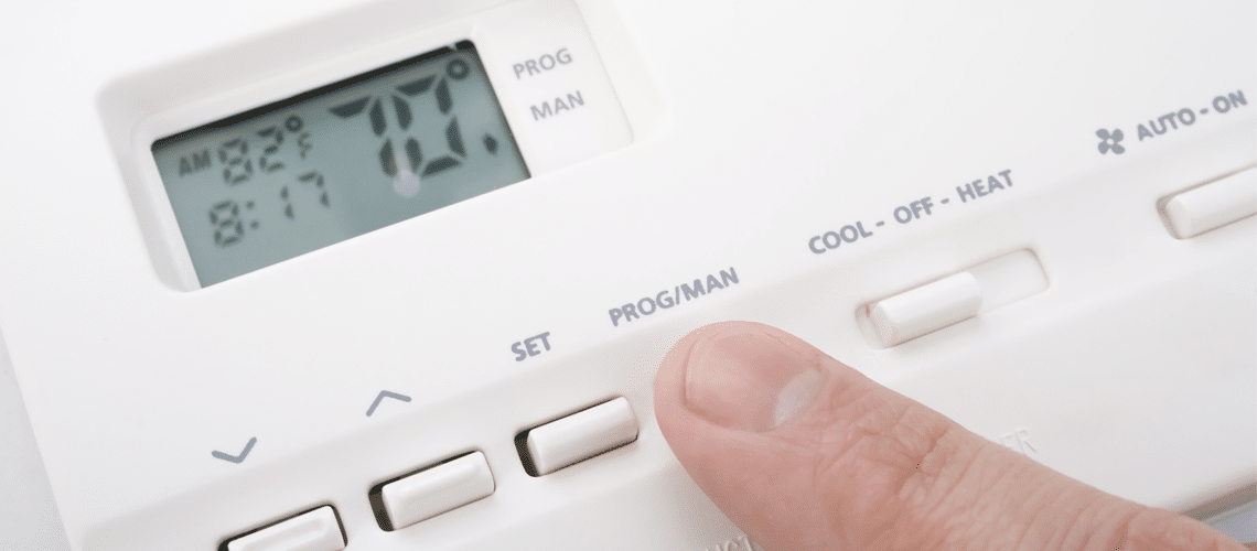 a finger pressing a button of a thermostat Air conditioner repair