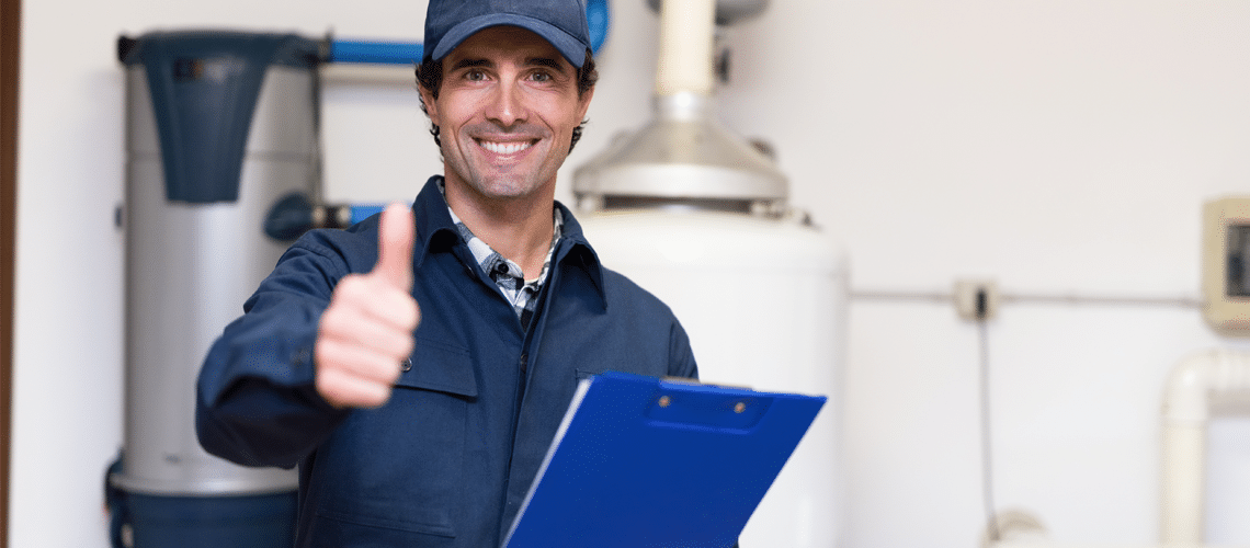 technician giving a thumbs up with a commercial boiler on the background