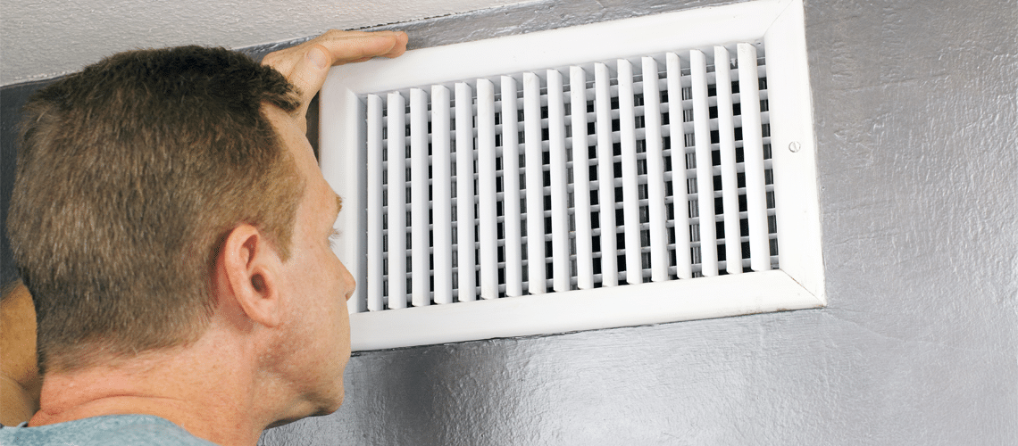 a man looking at an HVAC vent to see if it in need of HVAC Repair