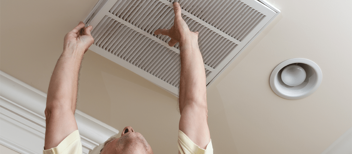 a man is reaching for the HVAC vent to see if HVAC repair is neccessary