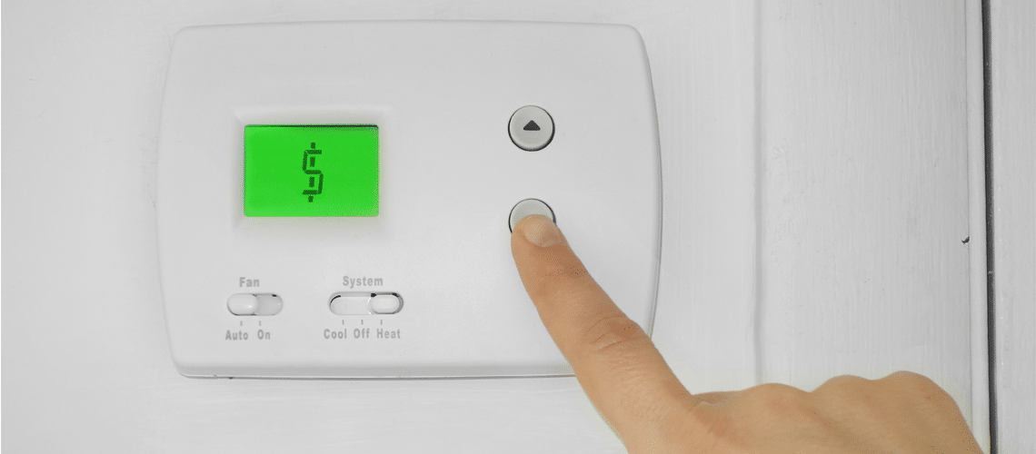 a finger pressing a button on a thermostat that displays a dollar symbol