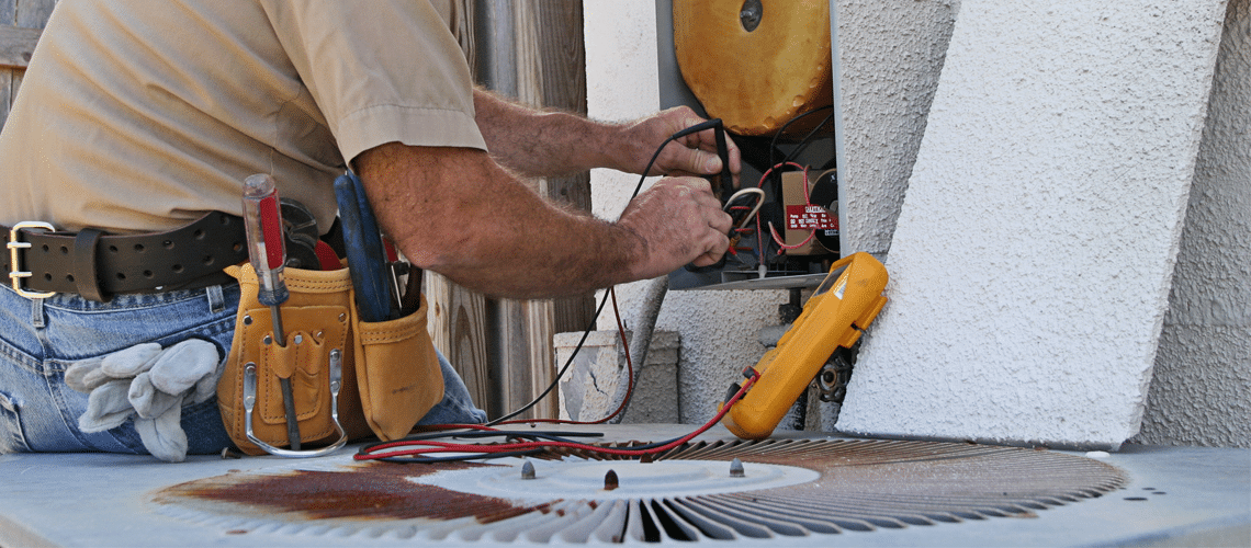 skilled technician from an HVAC company is making repairs to a component of an HVAC