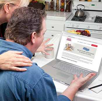 Couple In Kitchen Using Laptop to Research Crystal Heating & Cooling iWave