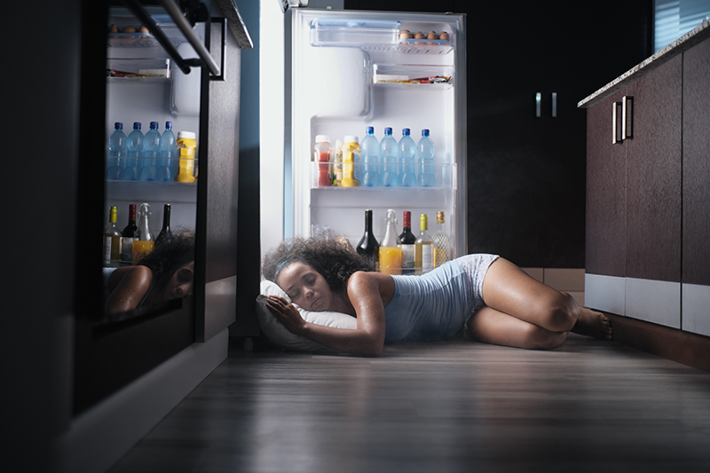 Black Woman cooling off with fridge